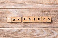 Palavra da declaração de rendimentos escrita no bloco de madeira texto da declaração de rendimentos na tabela de madeira para seu imagem de stock royalty free