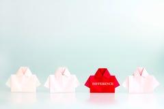 Palavra da diferença em um vermelho entre o papel branco da camisa do origâmi, uni imagem de stock