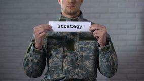 Palavra da estratégia escrita nas mãos do soldado masculino, plano do sinal dentro de batalha, defesa vídeos de arquivo