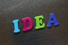 Palavra da ideia soletrada para fora usando ímãs coloridos do refrigerador Fotos de Stock