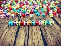 Palavra da INTRODUÇÃO de alfabetos coloridos do cubo no fundo de madeira foto de stock