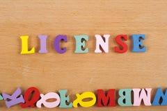 Palavra da LICENÇA no fundo de madeira composto das letras de madeira do bloco colorido do alfabeto do ABC, espaço da cópia para  fotografia de stock royalty free