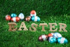 Palavra da Páscoa no projeto de madeira com chocolate do ovo na grama verde, Imagens de Stock Royalty Free