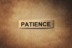 Palavra da paciência com papel de riscos imagem de stock
