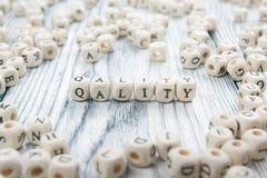Palavra da QUALIDADE escrita no bloco de madeira ABC de madeira Foto de Stock Royalty Free