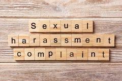 Palavra da queixa do acosso sexual escrita no bloco de madeira Texto na tabela, conceito da queixa do acosso sexual fotografia de stock