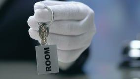 Palavra da sala no keychain na mão do administrador, material amigável, conceito do convite filme