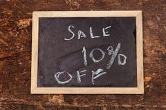 Palavra da venda escrita no quadro no fundo de madeira Imagem de Stock