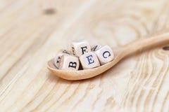 Palavra da vitamina das vistas superiores feita das letras de madeira na tabela e do A B C D E na colher de madeira Imagem de Stock Royalty Free