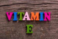 Palavra da vitamina E feita de letras de madeira fotografia de stock royalty free