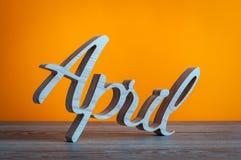 A palavra de abril cinzelou as letras de madeira no fundo alaranjado Imagens de Stock