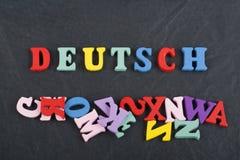 Palavra de DEUTSCH no fundo preto composto das letras de madeira do bloco colorido do alfabeto do ABC, espaço da placa da cópia p Fotografia de Stock Royalty Free