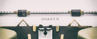 Palavra de GRAZIE em maiúsculo em uma folha da máquina de escrever Imagens de Stock Royalty Free