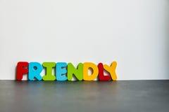 Palavra de madeira colorida amigável com background1 branco Foto de Stock