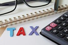 Palavra de madeira IMPOSTO, papel do caderno e calculadora na tabela da mesa de escritório imagem de stock royalty free