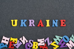 Palavra de UCRÂNIA no fundo preto composto das letras de madeira do bloco colorido do alfabeto do ABC, espaço da placa da cópia p Imagens de Stock