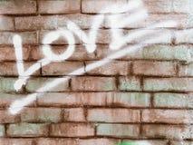 Palavra do amor na parede de tijolo Fotos de Stock