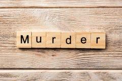 Palavra do assassinato escrita no bloco de madeira texto na tabela, conceito do assassinato imagem de stock royalty free