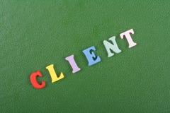 Palavra do CLIENTE no fundo verde composto das letras de madeira do bloco colorido do alfabeto do ABC, espaço da cópia para o tex fotografia de stock