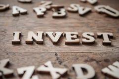 Palavra do conceito com alfabeto de madeira das letras - invista Imagem de Stock Royalty Free