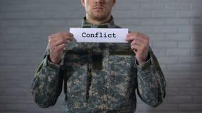 Palavra do conflito escrita nas mãos do soldado, anexação militar do sinal dentro, guerra filme