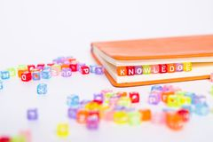 Palavra do CONHECIMENTO no bloco colorido do grânulo como o marcador no livro Conceito da instrução e do conhecimento imagem de stock