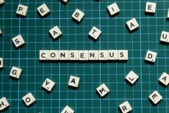 Palavra do consenso feita do bloco quadrado da letra no fundo quadrado verde da esteira imagens de stock