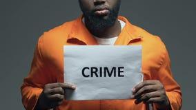 Palavra do crime no cartão nas mãos do prisioneiro preto, punição ilegal do ato filme