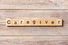 Palavra do cuidador escrita no bloco de madeira Texto na tabela, conceito do cuidador imagens de stock royalty free