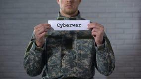 Palavra do Cyberwar escrita nas mãos do soldado masculino, segurança da informação do sinal dentro video estoque
