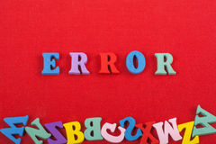 Palavra do ERRO no fundo vermelho composto das letras de madeira do bloco colorido do alfabeto do ABC, espaço da cópia para o tex Imagem de Stock Royalty Free