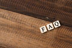 Palavra do FAQ em telhas do alfabeto na tabela de madeira peça frequentemente o conceito das perguntas foto de stock royalty free