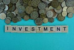 Palavra do investimento das letras de madeira perto de uma pilha das moedas Imagem de Stock