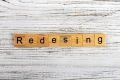 Palavra do REDESIGN feita com conceito de madeira dos blocos imagens de stock