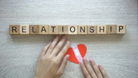 Palavra do relacionamento em cubos de madeira, mãos fêmeas que põem o remendo sobre o coração de papel vídeos de arquivo
