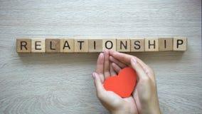 Palavra do relacionamento feita dos cubos, mãos fêmeas que guardam o coração do papel, romance video estoque
