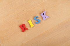 Palavra do RISCO no fundo de madeira composto das letras de madeira do bloco colorido do alfabeto do ABC, espaço da cópia para o  Imagem de Stock