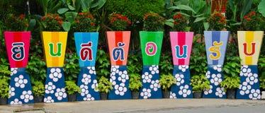 Palavra do sinal de boas-vindas em potenciômetros de flor Foto de Stock