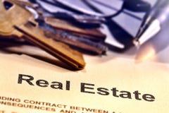 Palavra do título de bens imobiliários em uma página do contrato do corretor de imóveis imagens de stock royalty free