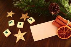 Palavra do Xmas com Livro Branco, vela da lanterna elétrica, estrela, ramo do pinho, canela e laranja Fotografia de Stock Royalty Free