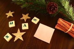Palavra do Xmas com Livro Branco, vela da lanterna elétrica, estrela, ramo do pinho e canela Imagem de Stock