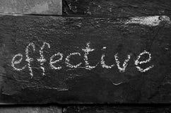 A palavra EFICAZ escrito com giz na pedra preta Fotos de Stock
