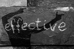 A palavra EFICAZ escrito com giz na pedra preta com sombra do homem nela Foto de Stock Royalty Free