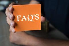 Palavra em um papel de nota alaranjado, conceito do ` s do FAQ do negócio Imagens de Stock