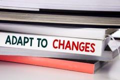 A palavra, escrevendo adapta-se às mudanças Conceito do negócio para o futuro novo da adaptação escrito no livro no fundo branco imagens de stock