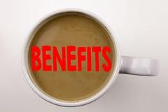 A palavra, escrevendo beneficia o texto no café no copo Conceito do negócio para benefícios financeiros do empregado do bônus no  fotos de stock