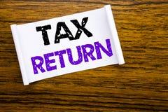 Palavra, escrevendo a declaração de rendimentos Conceito do negócio para o reembolso da tributação escrito no papel de nota pegaj imagens de stock royalty free