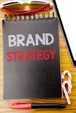 Palavra, escrevendo a estratégia do tipo Conceito do negócio para o plano de mercado escrito no livro do caderno, fundo de madeir Imagens de Stock Royalty Free