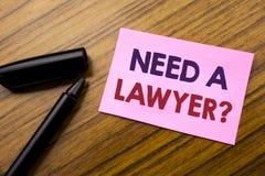 Palavra, escrevendo a necessidade um advogado Conceito do negócio para justiça Help Written da defesa no papel vermelho da nota p foto de stock royalty free
