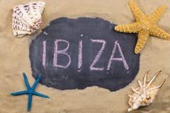 Palavra escrita à mão IBIZA escrita no giz, entre conchas do mar e estrelas do mar fotografia de stock